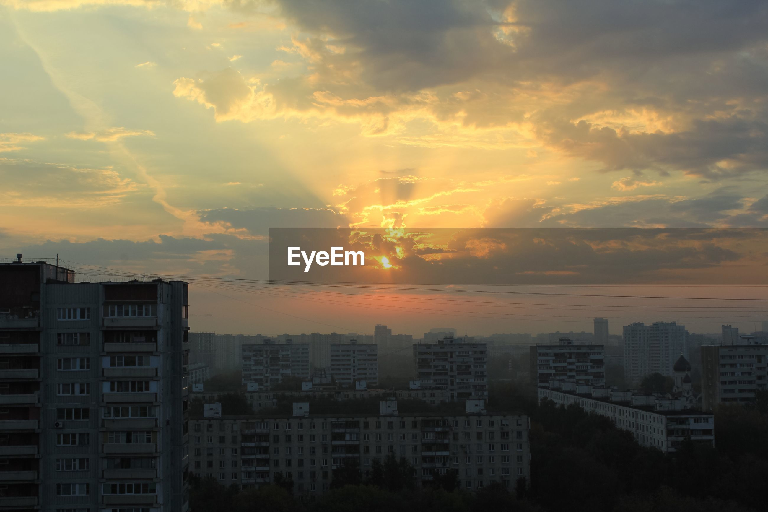 HIGH ANGLE VIEW OF BUILDINGS AGAINST SKY AT SUNSET
