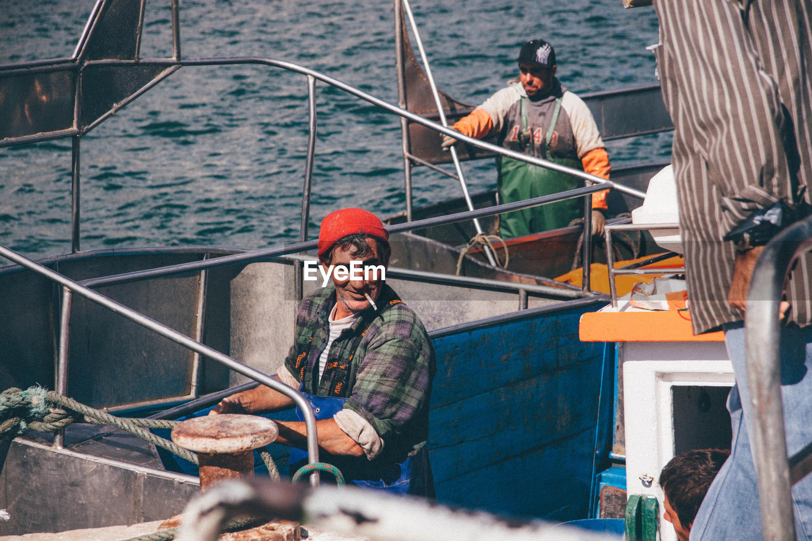 MAN SITTING ON RAILING OF SHIP