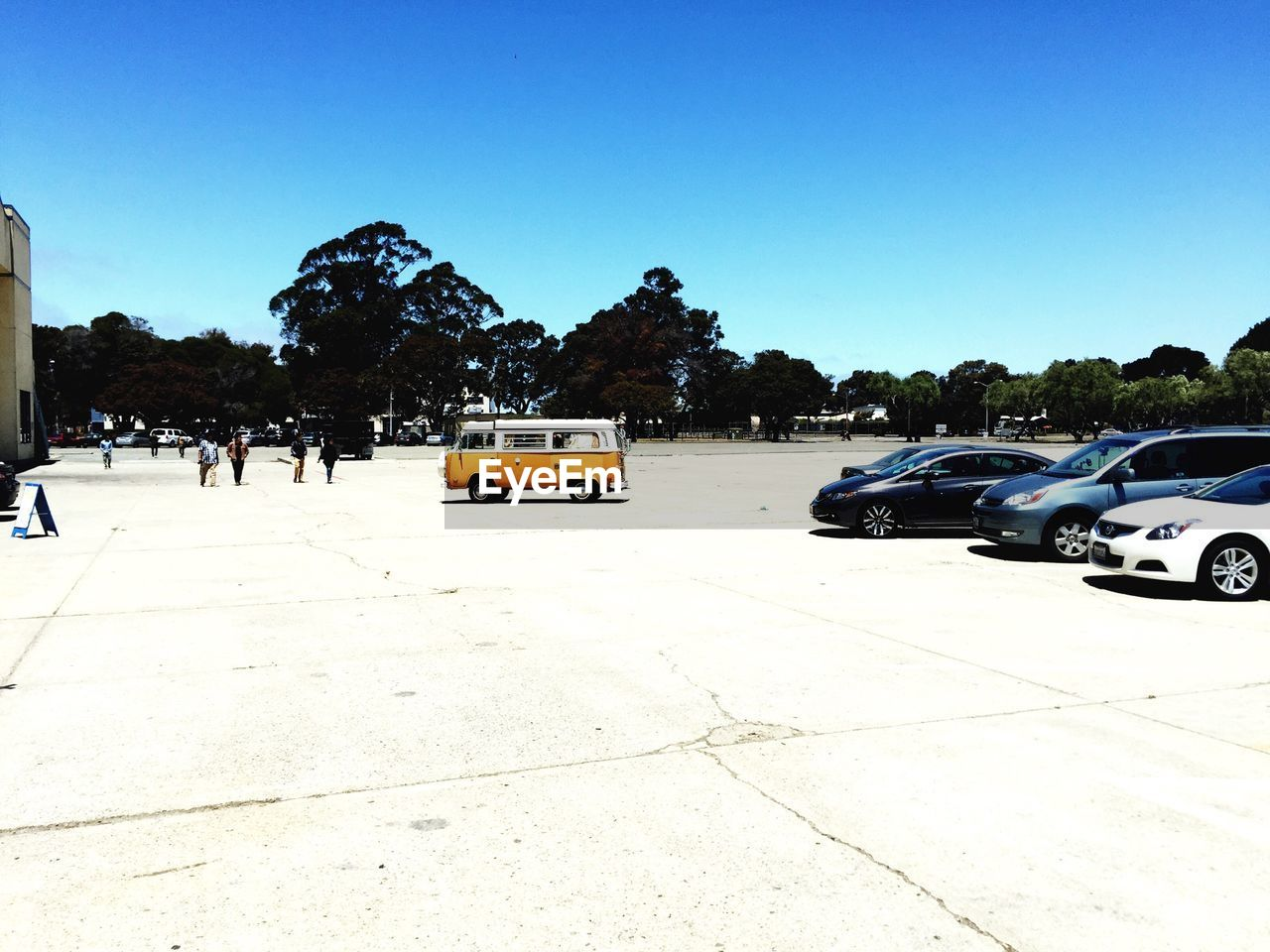 Vehicles parked on road against clear blue sky