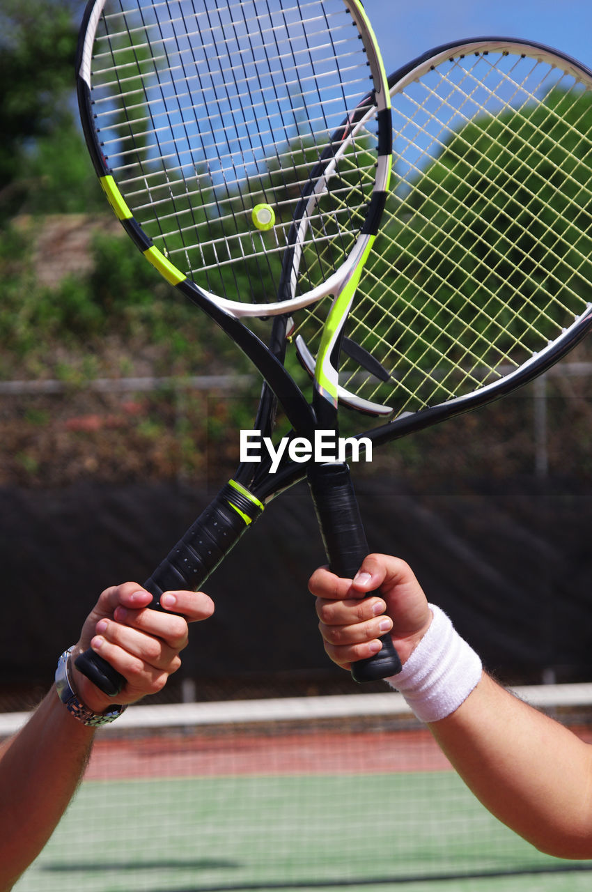 Close-up of cropped hands with tennis racket