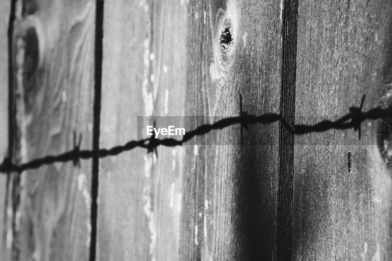 Close-up of barbed wire against wood