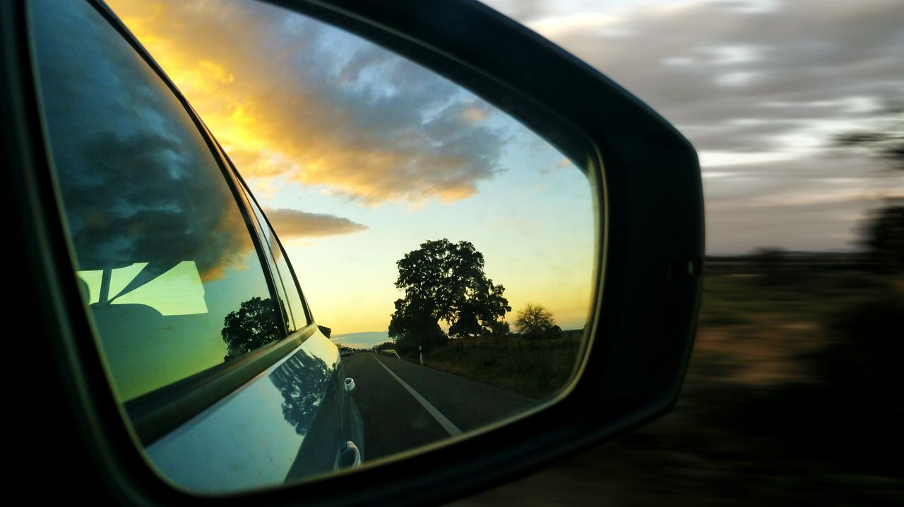 sky, cloud - sky, glass - material, mode of transportation, transportation, land vehicle, sunset, reflection, nature, car, side-view mirror, tree, motor vehicle, plant, vehicle interior, transparent, road, no people, close-up, window, outdoors, vehicle mirror