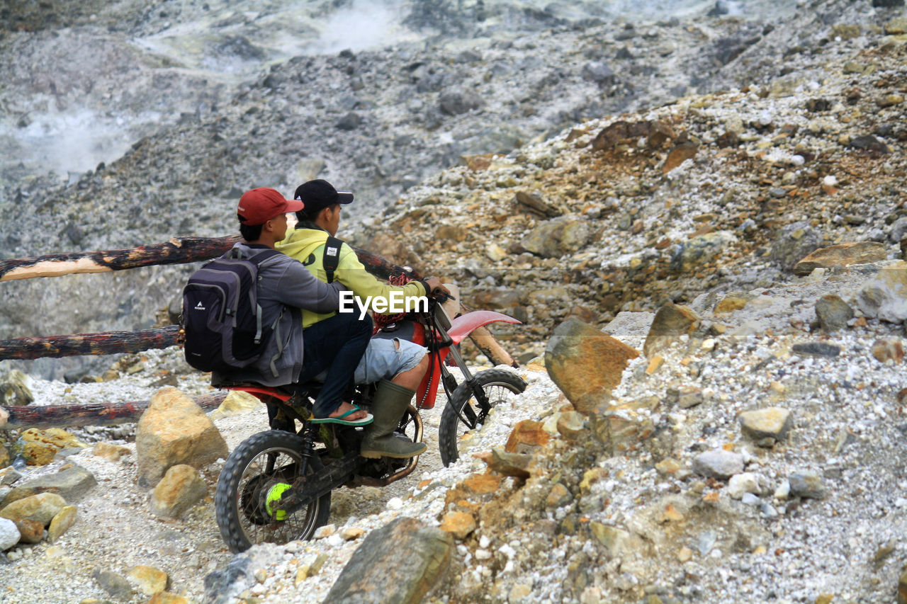 two people, rock - object, adventure, real people, leisure activity, rear view, mountain, togetherness, men, backpack, outdoors, challenge, nature, climbing, day, lifestyles, women, sitting, rock climbing, extreme sports, full length, beauty in nature, headwear, teamwork, adult, cycling helmet, people, adults only