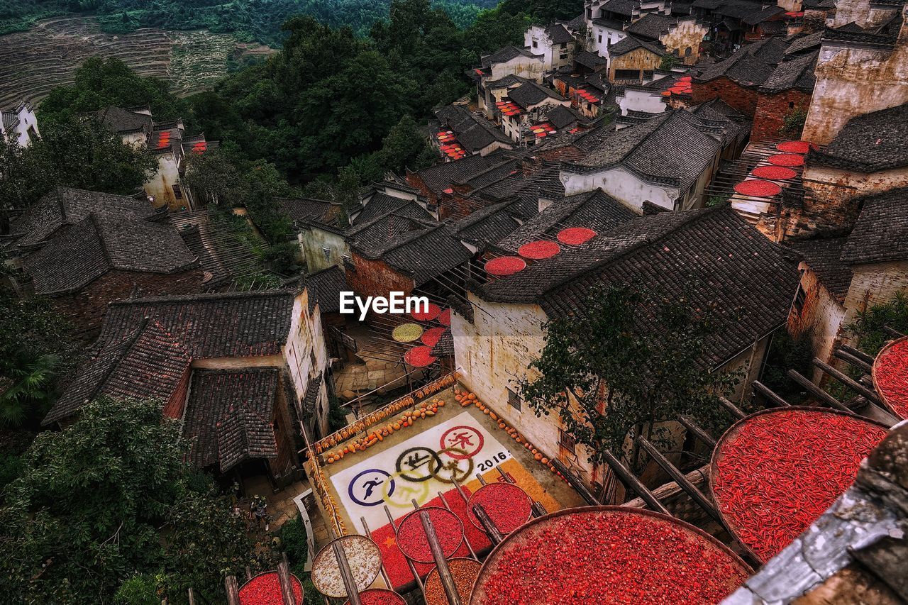 High Angle View Of Red Chili Peppers In Wicker Containers On House Roofs