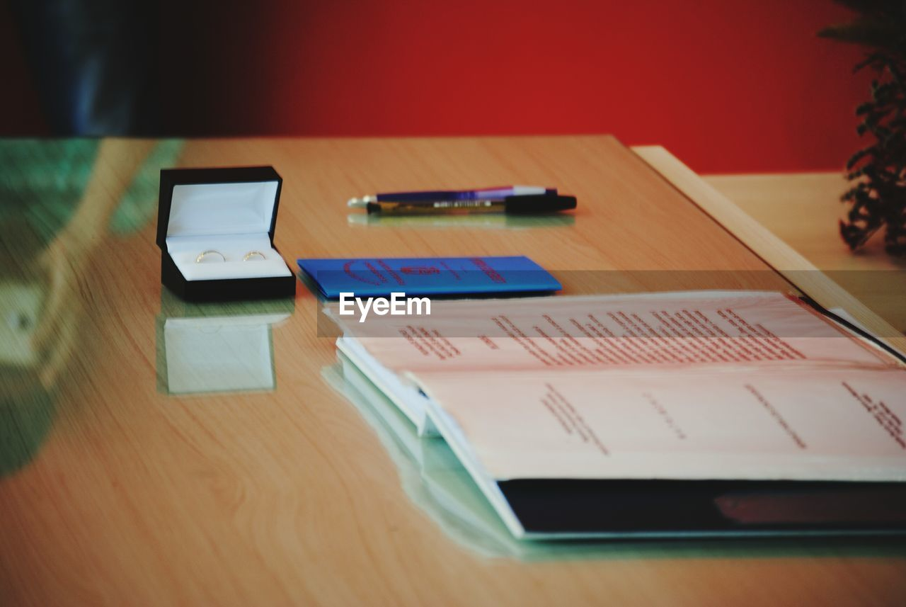 table, indoors, wireless technology, communication, technology, still life, no people, selective focus, portable information device, connection, wood - material, close-up, smart phone, mobile phone, high angle view, education, pen, focus on foreground, screen, device screen
