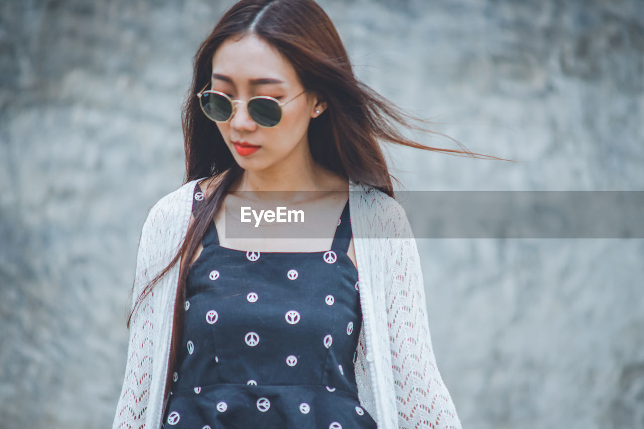 Young woman wearing sunglasses while standing outdoors