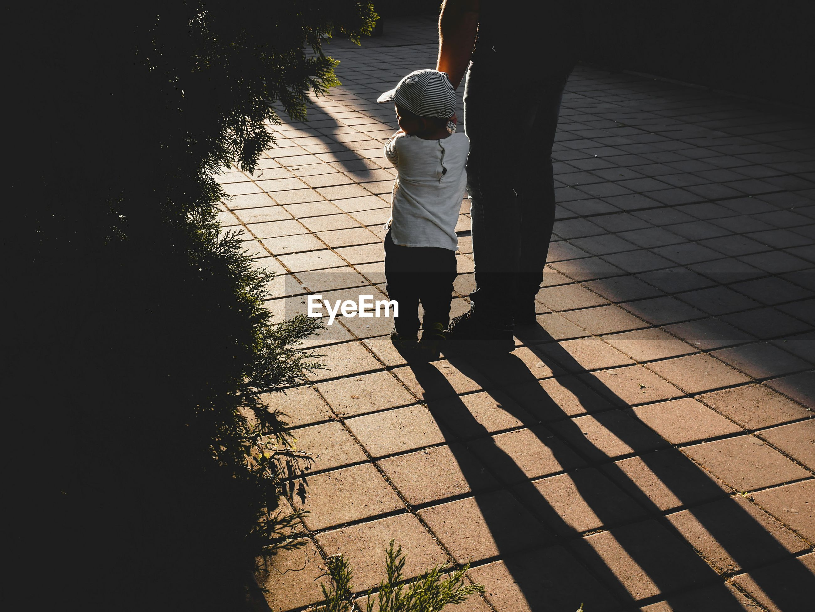 Low section of father standing with son on footpath