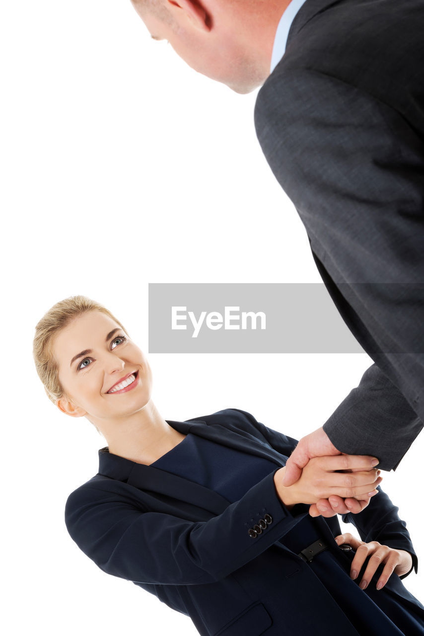 Smiling Colleagues Shaking Hands Against White Background