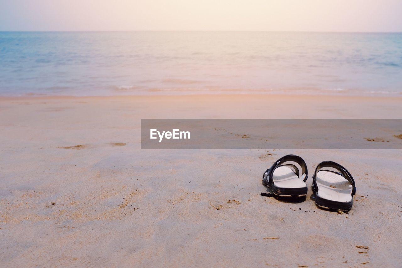 Sandals on sand at beach against sky