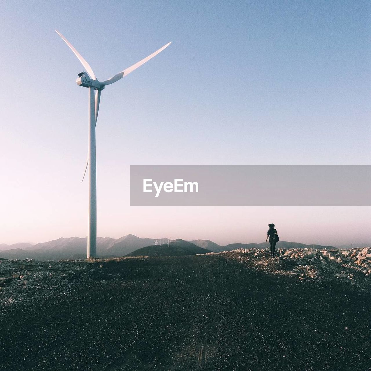 wind turbine, wind power, nature, alternative energy, one person, outdoors, landscape, beauty in nature, fuel and power generation, real people, standing, scenics, mountain, day, clear sky, technology, sky, windmill, men, industrial windmill, people
