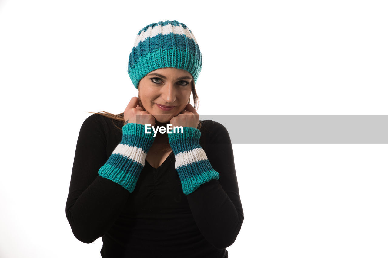 Portrait Of Young Woman In Knit Hat Standing Against White Background