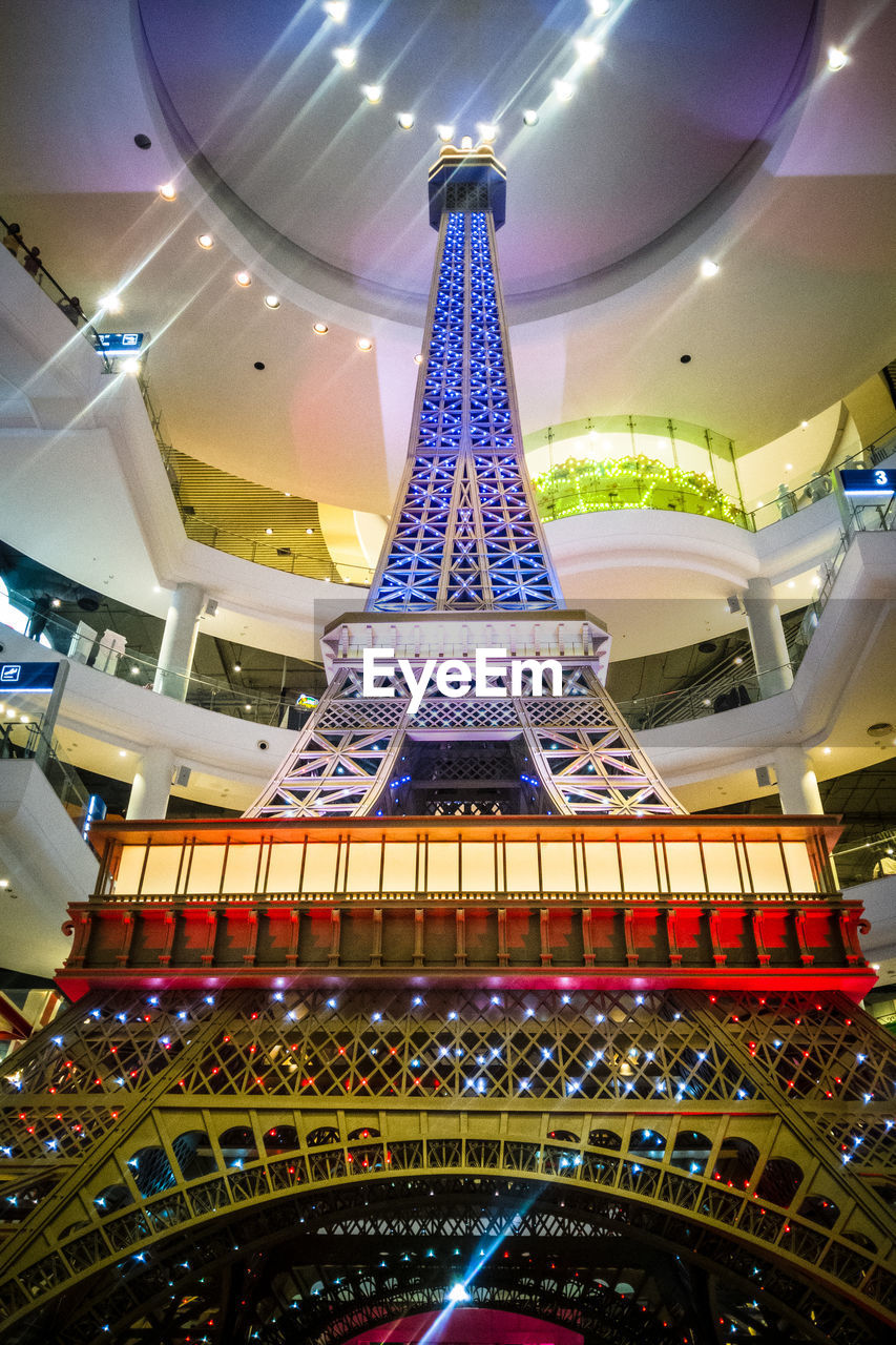 architecture, built structure, illuminated, low angle view, ceiling, travel destinations, indoors, modern, no people, city, tower, metal, architectural feature, tall - high, lighting equipment, shopping mall, city life, travel, luxury