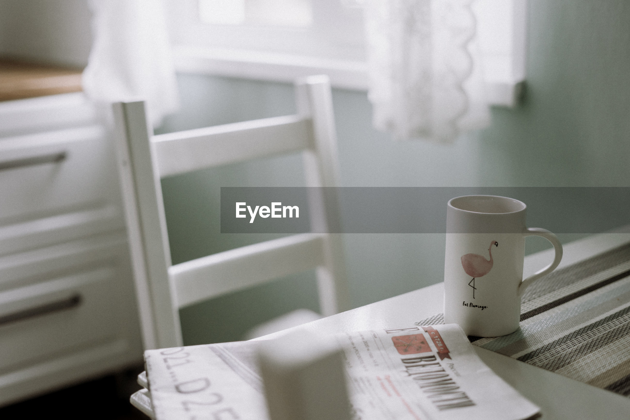 Coffee cup and newspaper on table at home
