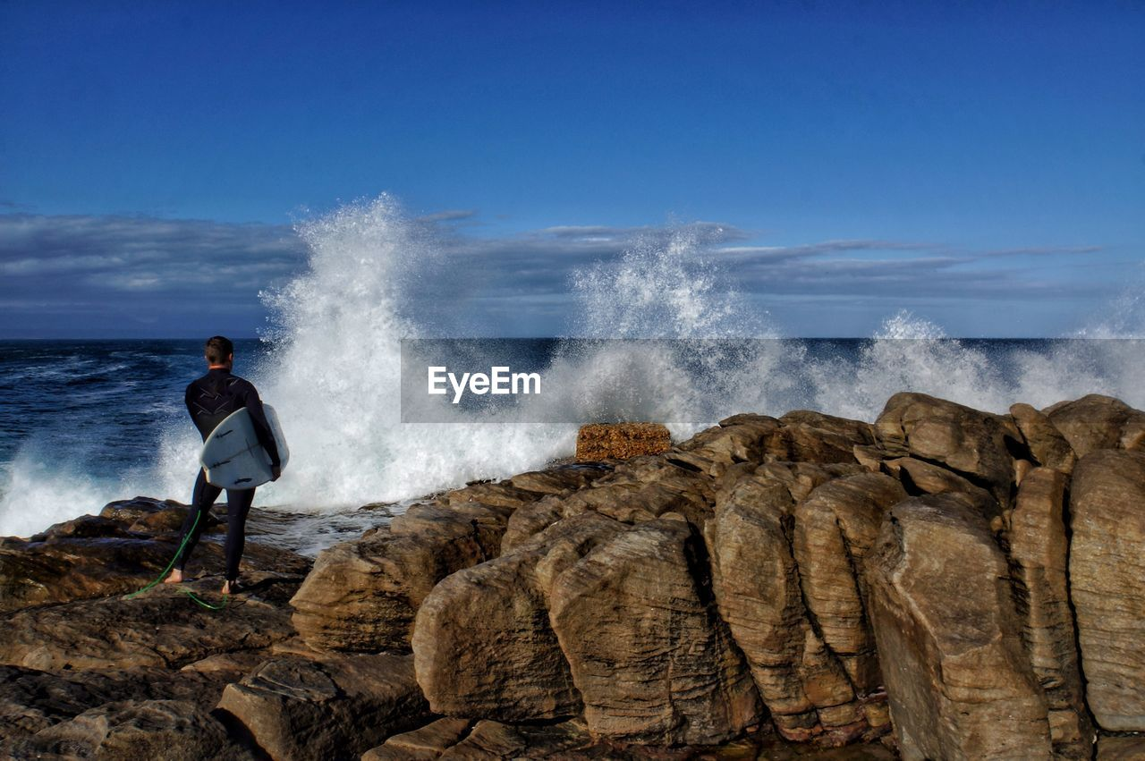 Rear View Of Man Standing At Sea Shore Against Clear Sky