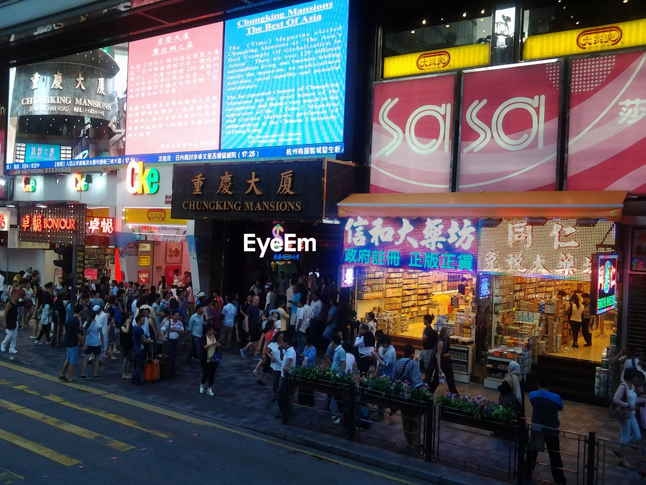 Crowd on city street against illuminated building
