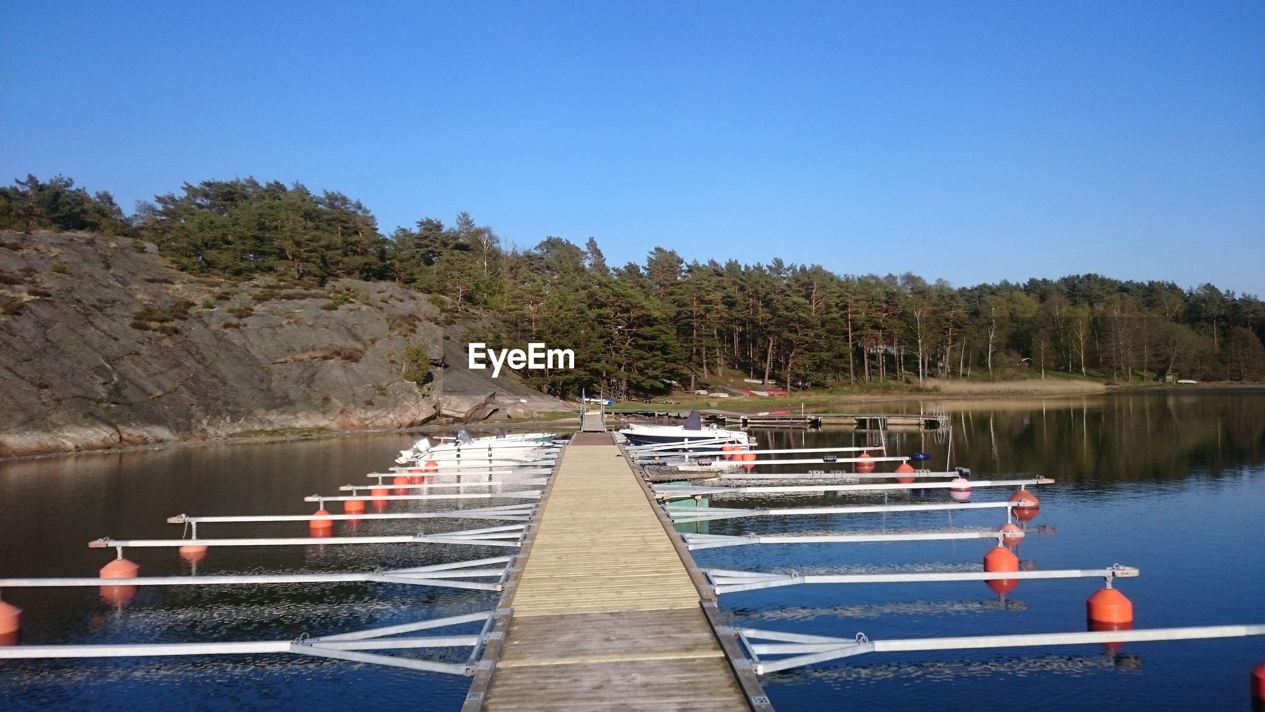 Pier amidst lake against clear blue sky