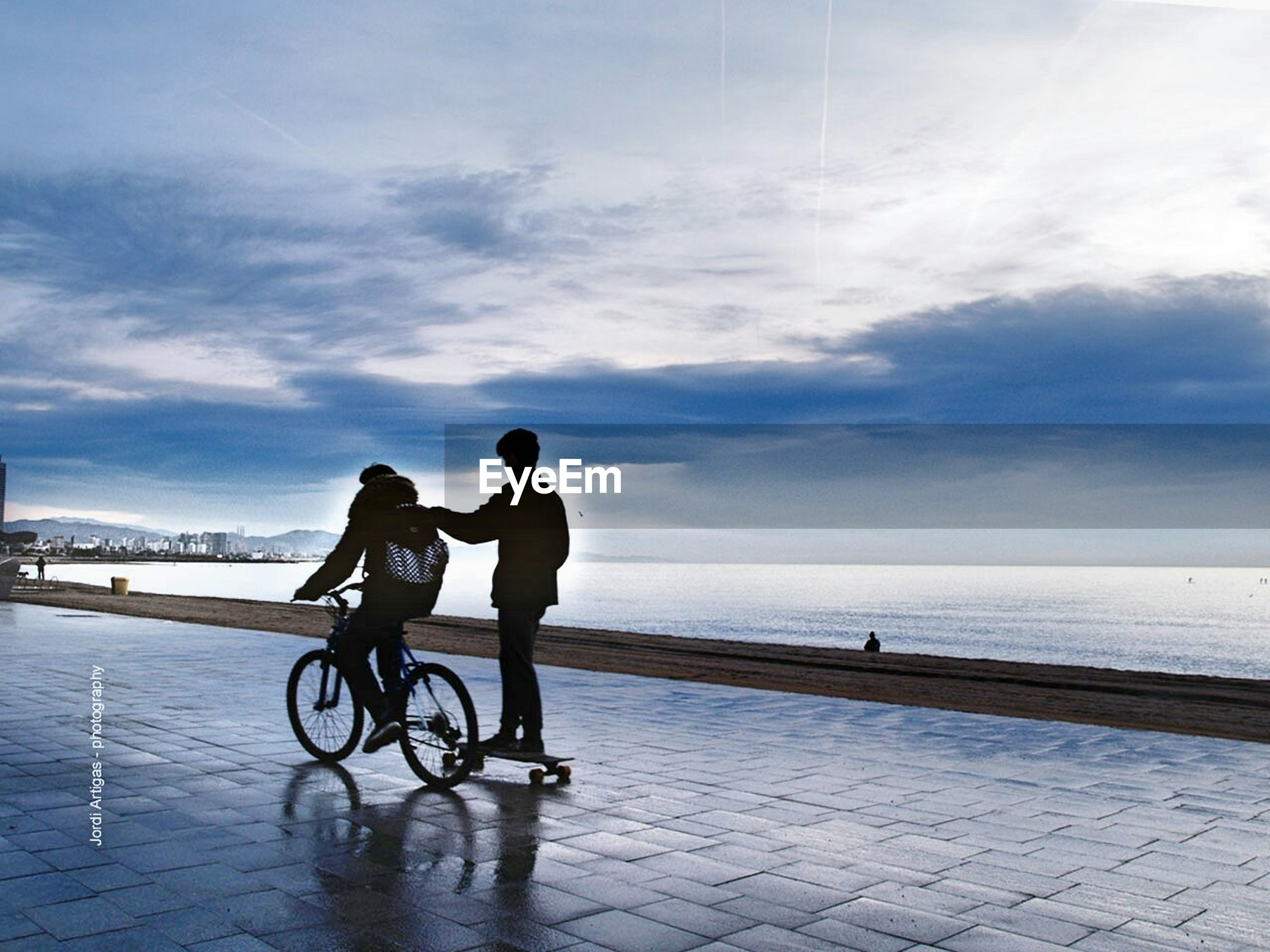 water, sea, sky, lifestyles, full length, men, leisure activity, horizon over water, cloud - sky, beach, bicycle, silhouette, transportation, togetherness, rear view, cloud, walking, shore