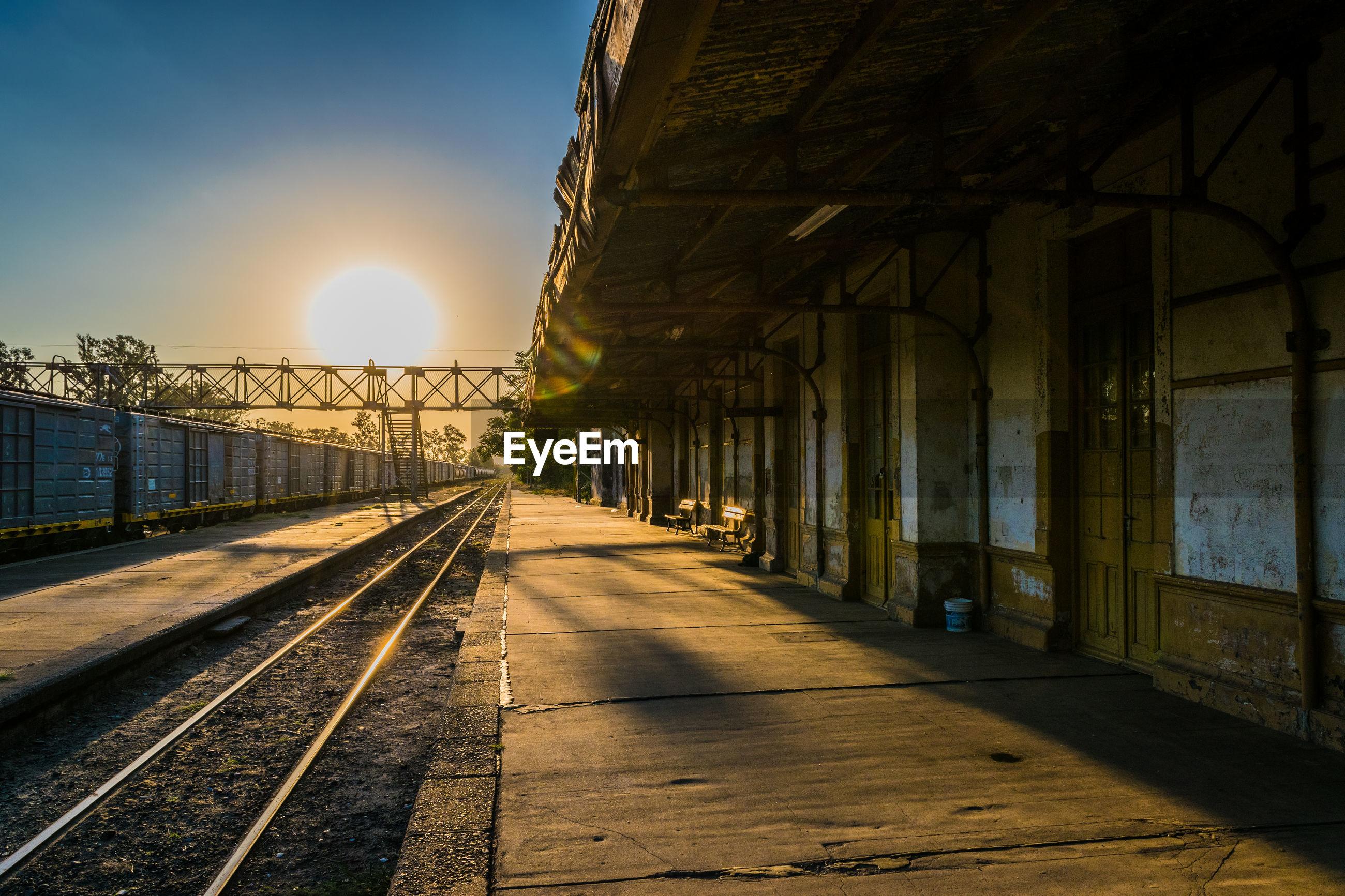 Empty railroad station platform during sunset