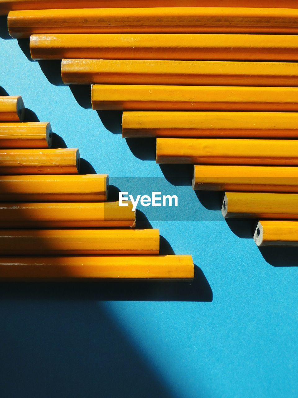Close-Up Of Yellow Pencils On Blue Table