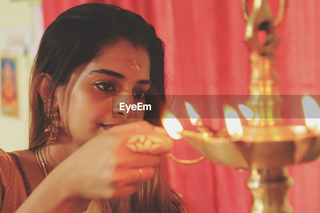 Young Woman Lighting Diya At Home
