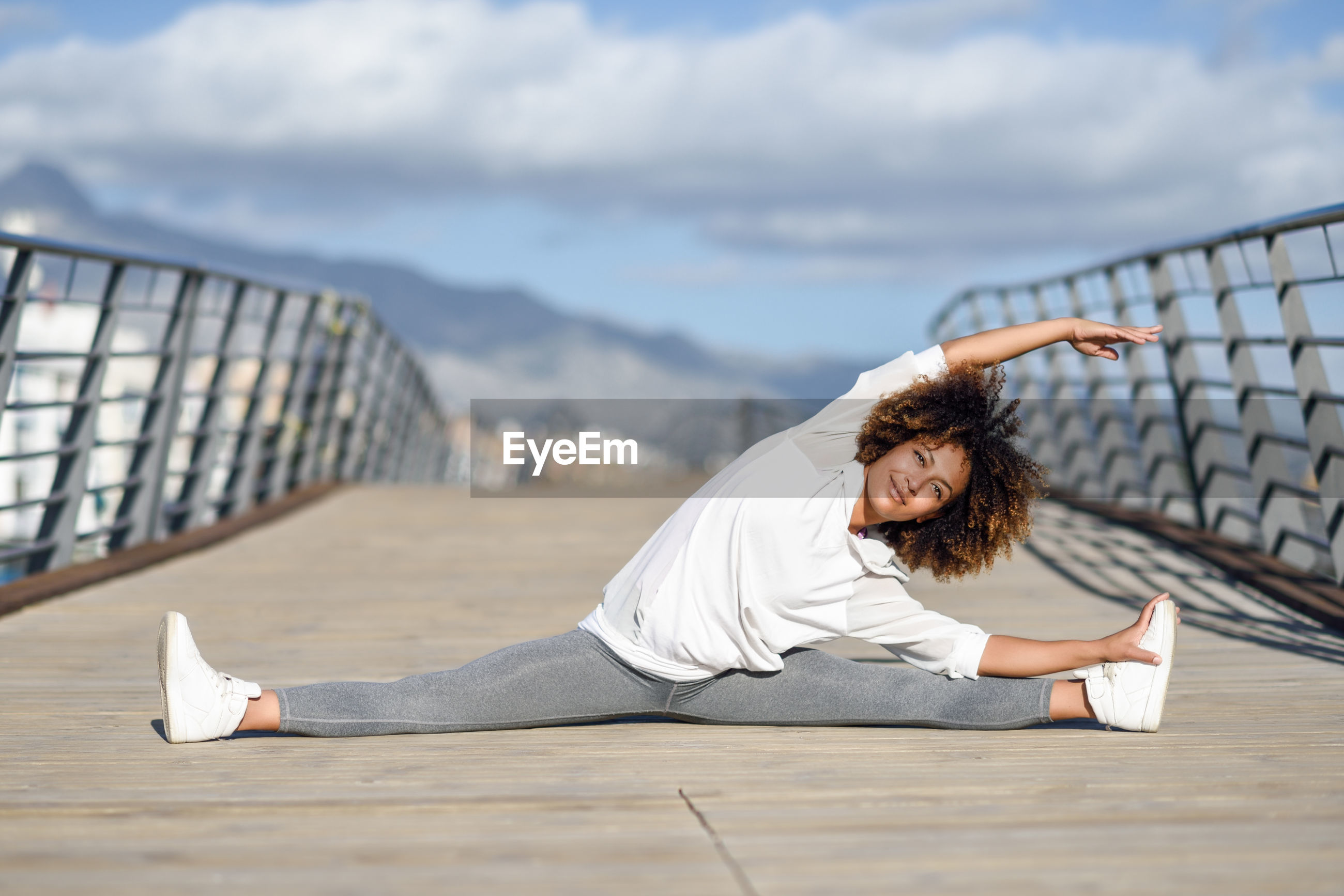 Full length of young woman exercising on bridge against sky