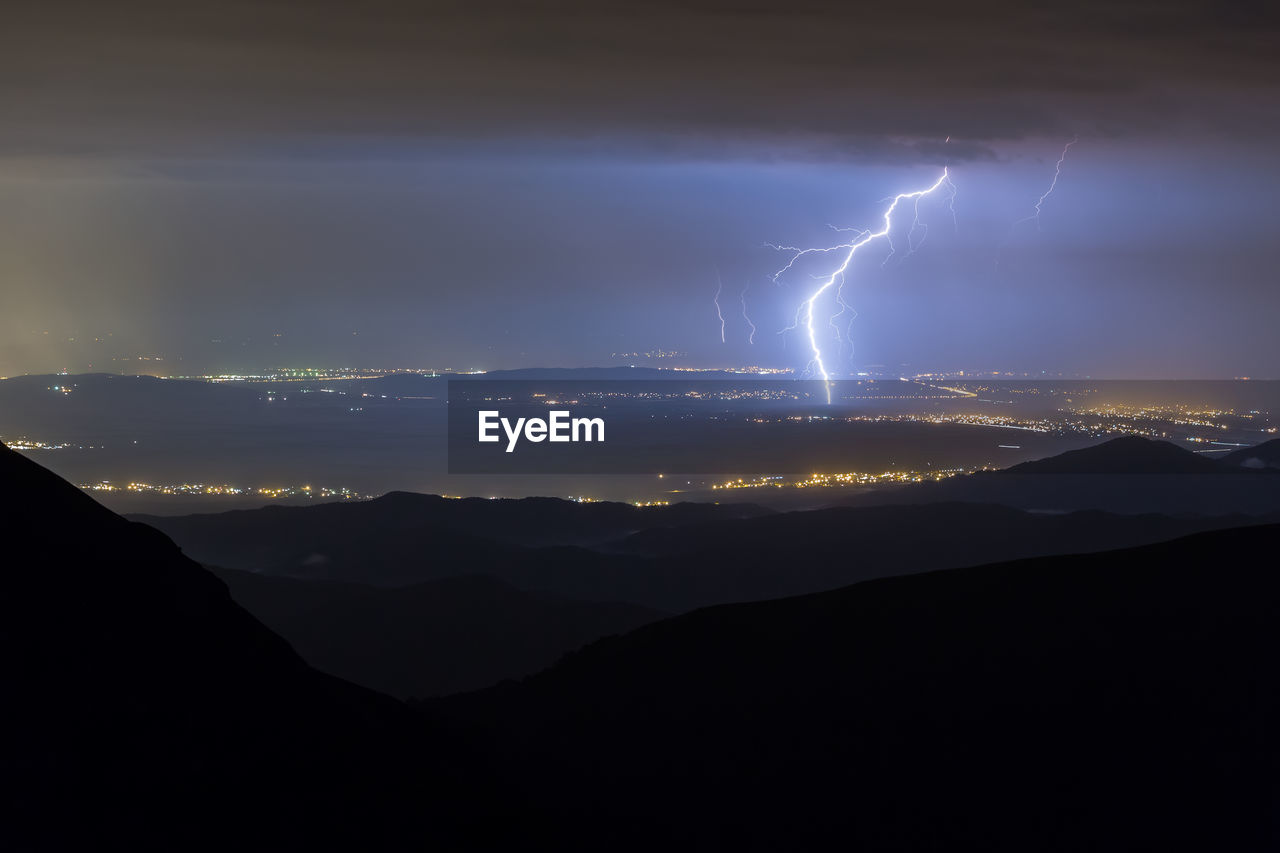 PANORAMIC VIEW OF LIGHTNING OVER ILLUMINATED MOUNTAINS AGAINST SKY