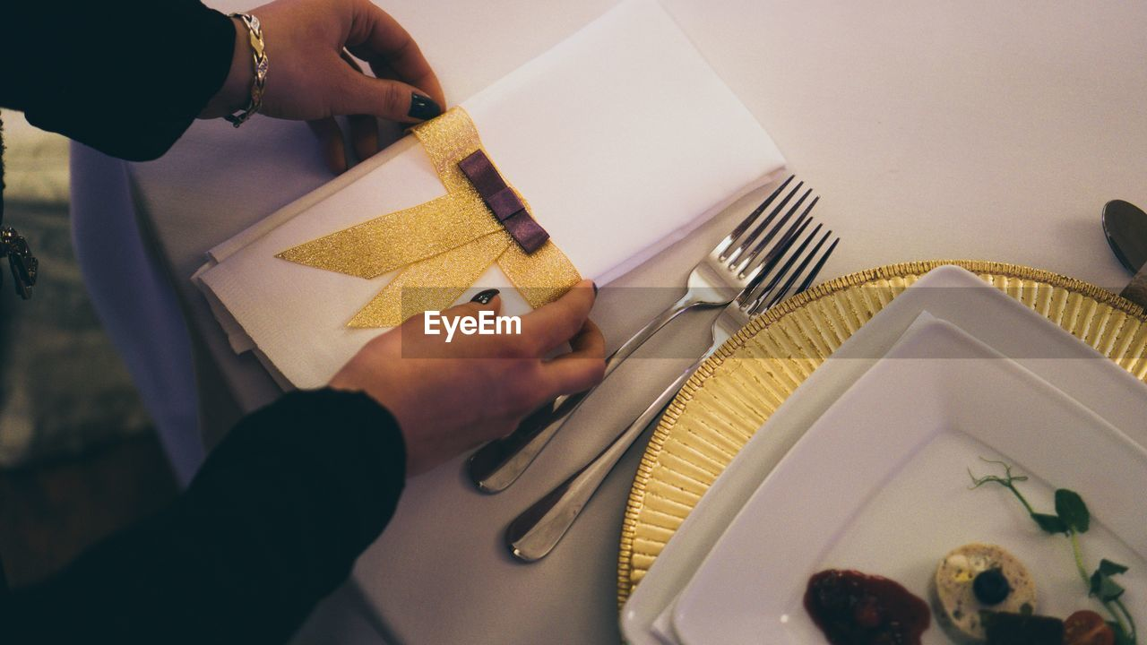 Cropped Hands Of Woman Arranging Napkin On Table