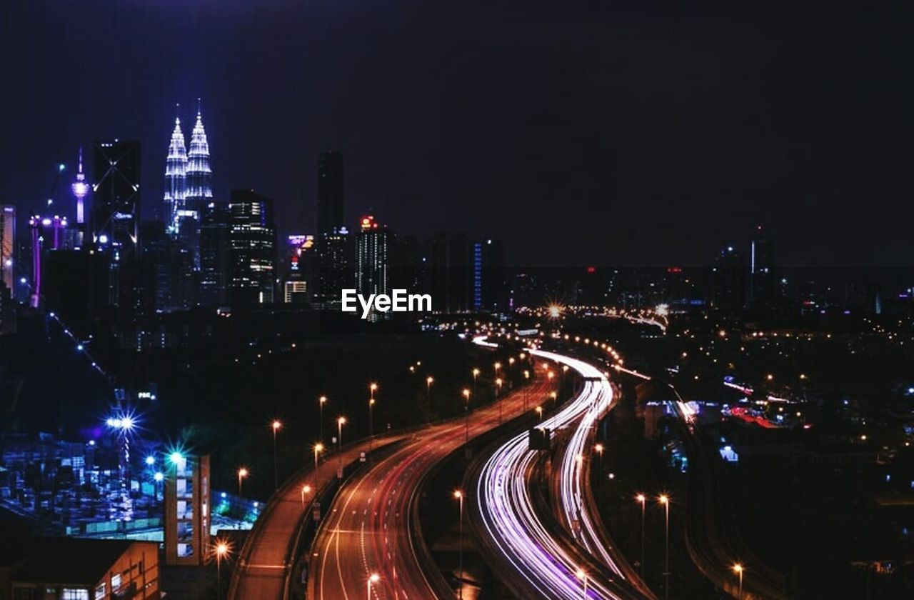 illuminated, night, city, speed, light trail, city life, transportation, cityscape, high angle view, skyscraper, building exterior, long exposure, motion, architecture, road, outdoors, travel destinations, no people, modern, urban skyline, high street, sky