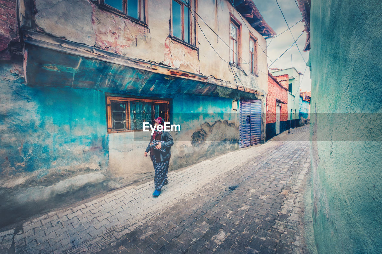 building exterior, architecture, one person, built structure, building, full length, city, residential district, street, lifestyles, real people, day, walking, standing, leisure activity, footpath, men, house, alley, outdoors