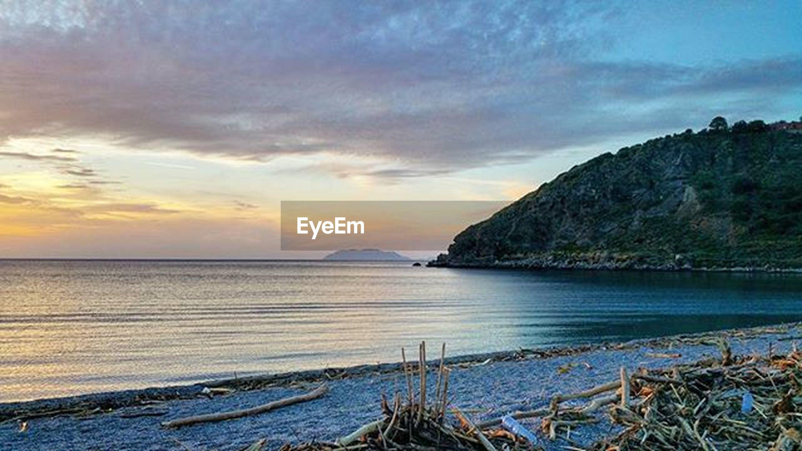 water, sea, tranquil scene, scenics, beauty in nature, tranquility, sky, horizon over water, sunset, nature, mountain, idyllic, cloud - sky, beach, cloud, shore, coastline, outdoors, rock - object, non-urban scene