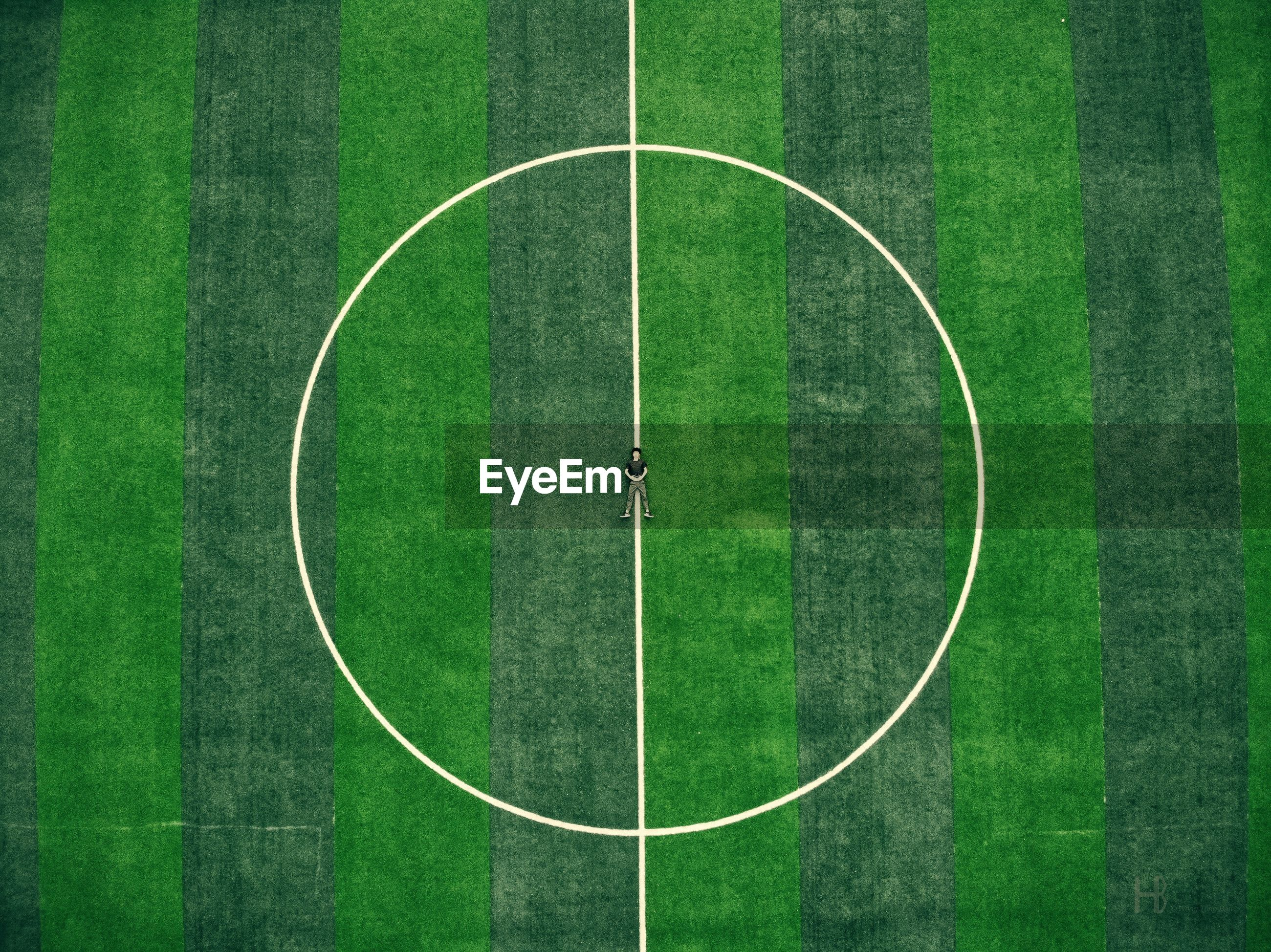 High angle view of man lying on soccer field