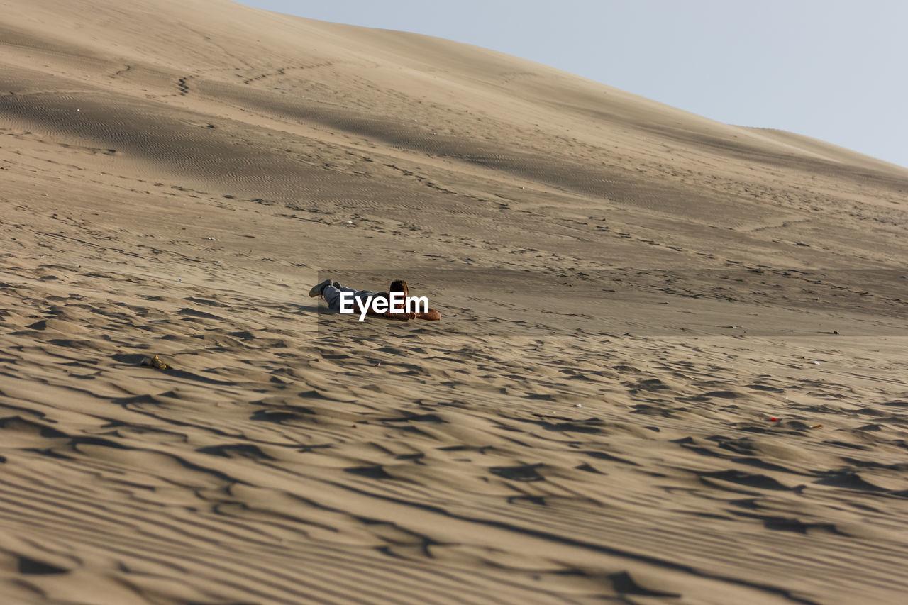 Man Lying On Sand At Desert