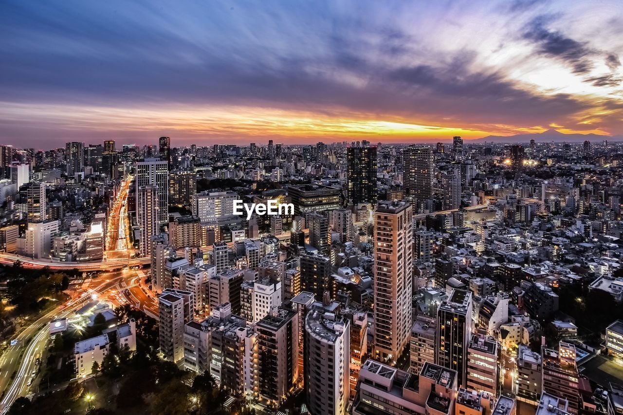building exterior, city, architecture, cityscape, built structure, sky, sunset, cloud - sky, crowded, building, crowd, high angle view, nature, residential district, illuminated, office building exterior, skyscraper, travel destinations, modern, outdoors