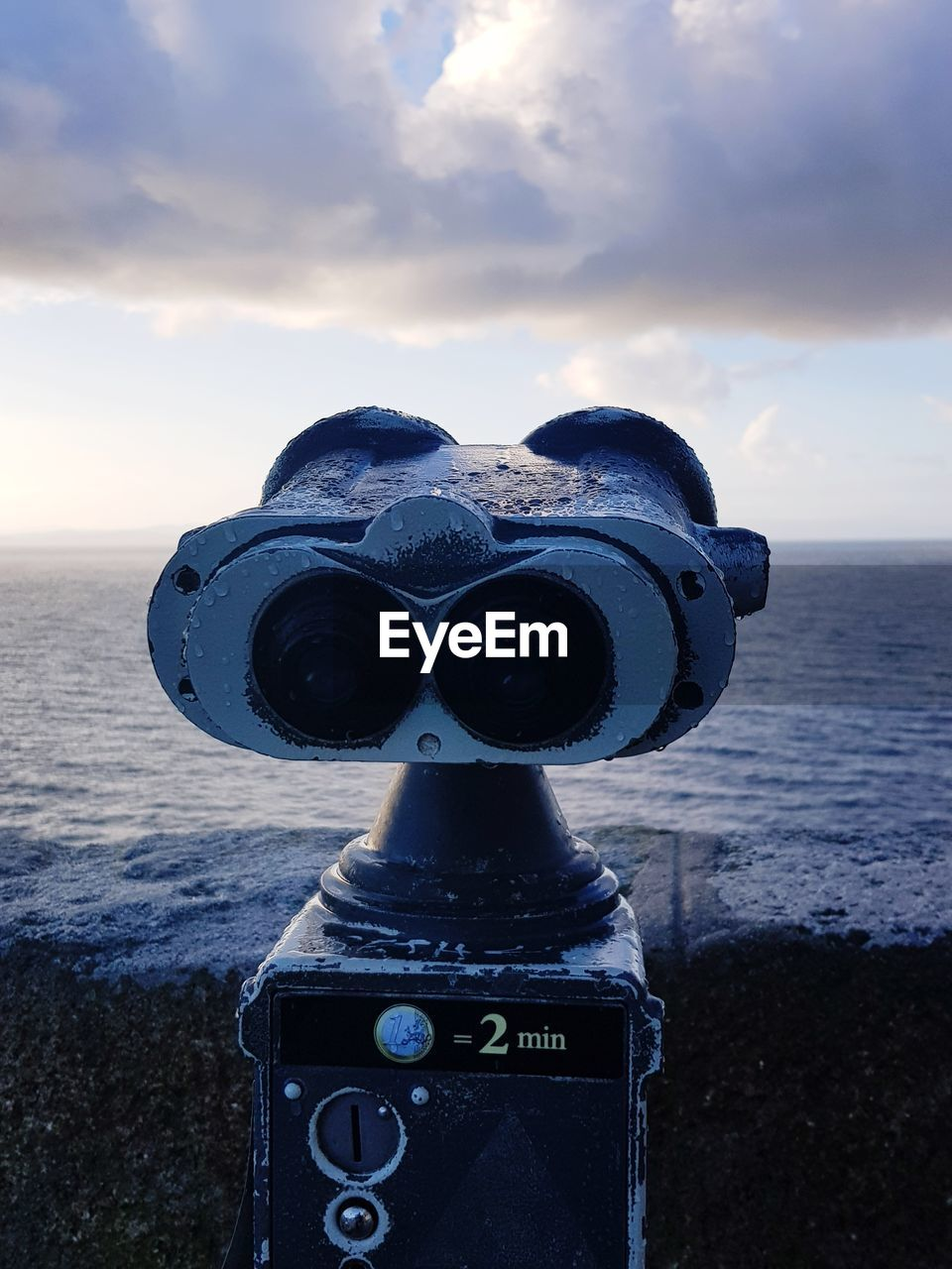 CLOSE-UP OF COIN-OPERATED BINOCULARS ON SEA SHORE