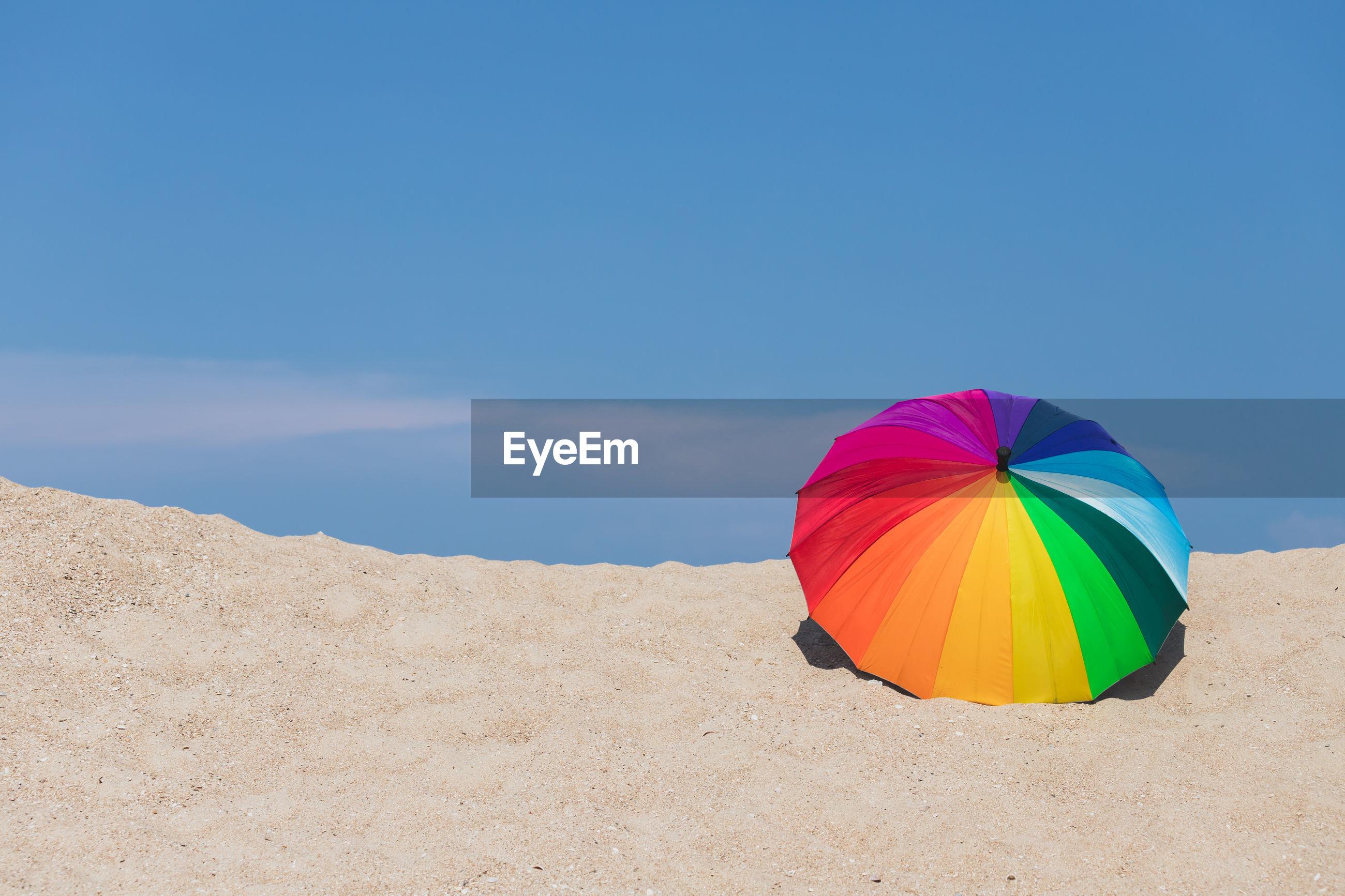 Multi colored umbrella on beach against blue sky
