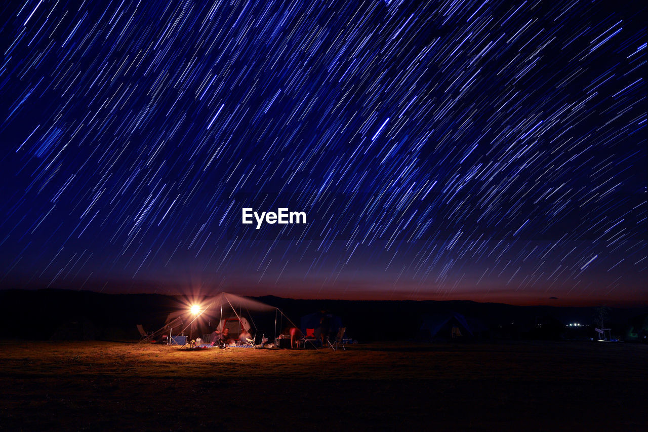 Scenic View Of Star Trails Over Field At Night
