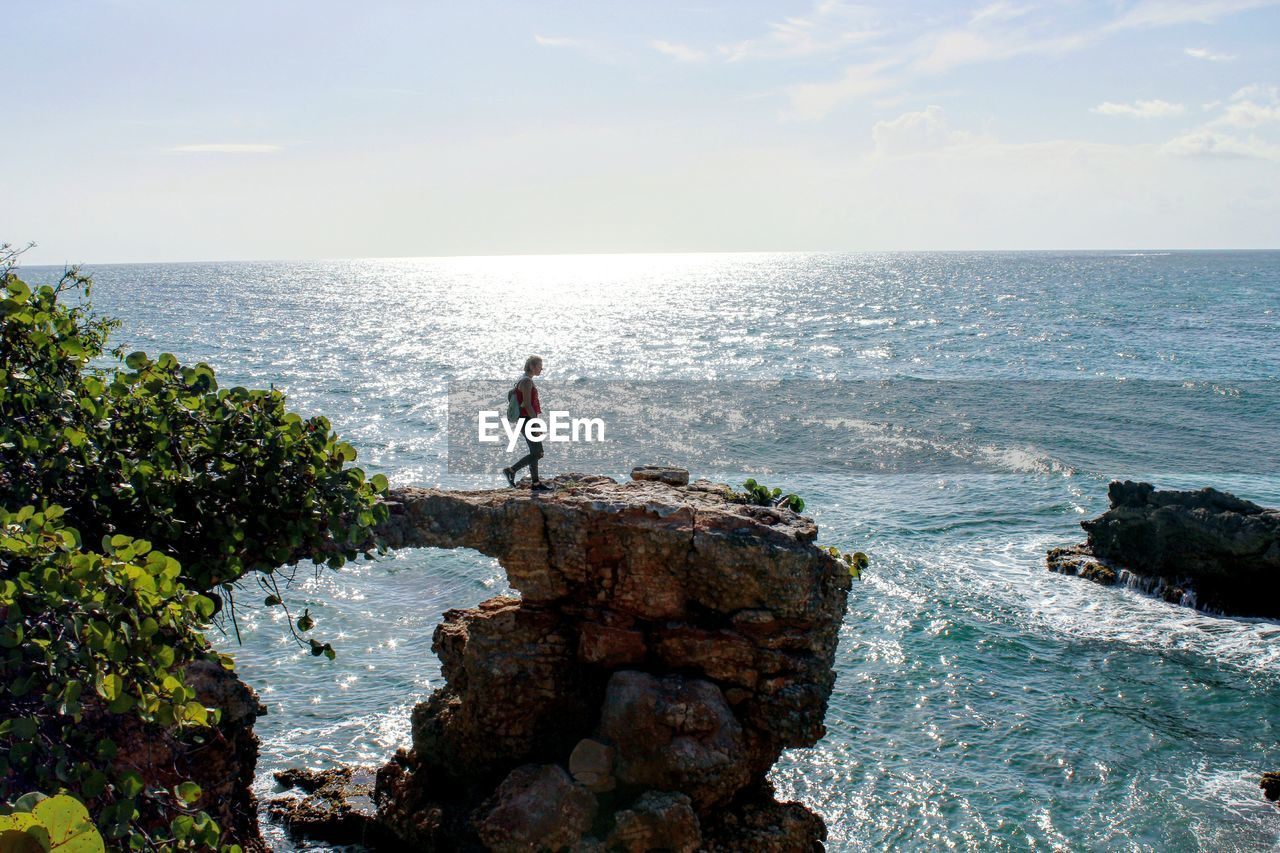 Woman Hiking On Rock Formation Over Sea Against Sky At Puente De Piedra