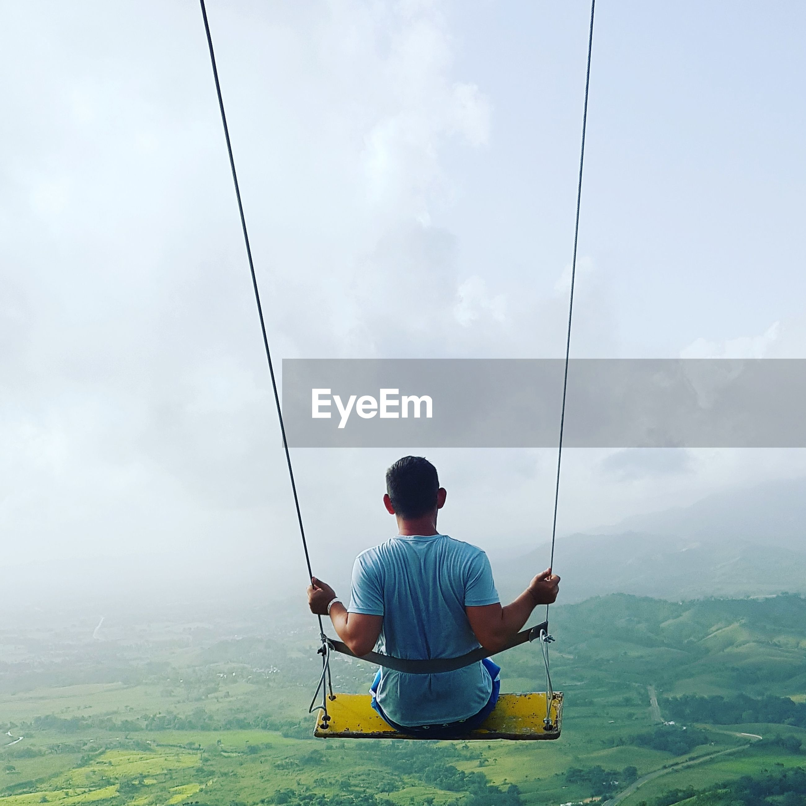 Rear view of man sitting on swing against sky