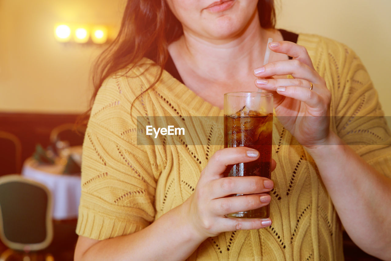 Midsection of mid adult woman holding ice tea in restaurant
