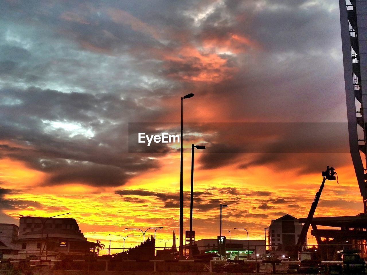 cloud - sky, sky, sunset, built structure, orange color, architecture, dramatic sky, building exterior, transportation, street light, no people, silhouette, city, outdoors, land vehicle, illuminated, nature, day
