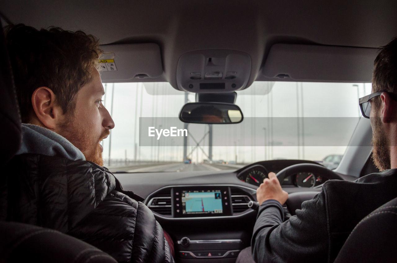 Rear view of men sitting in car