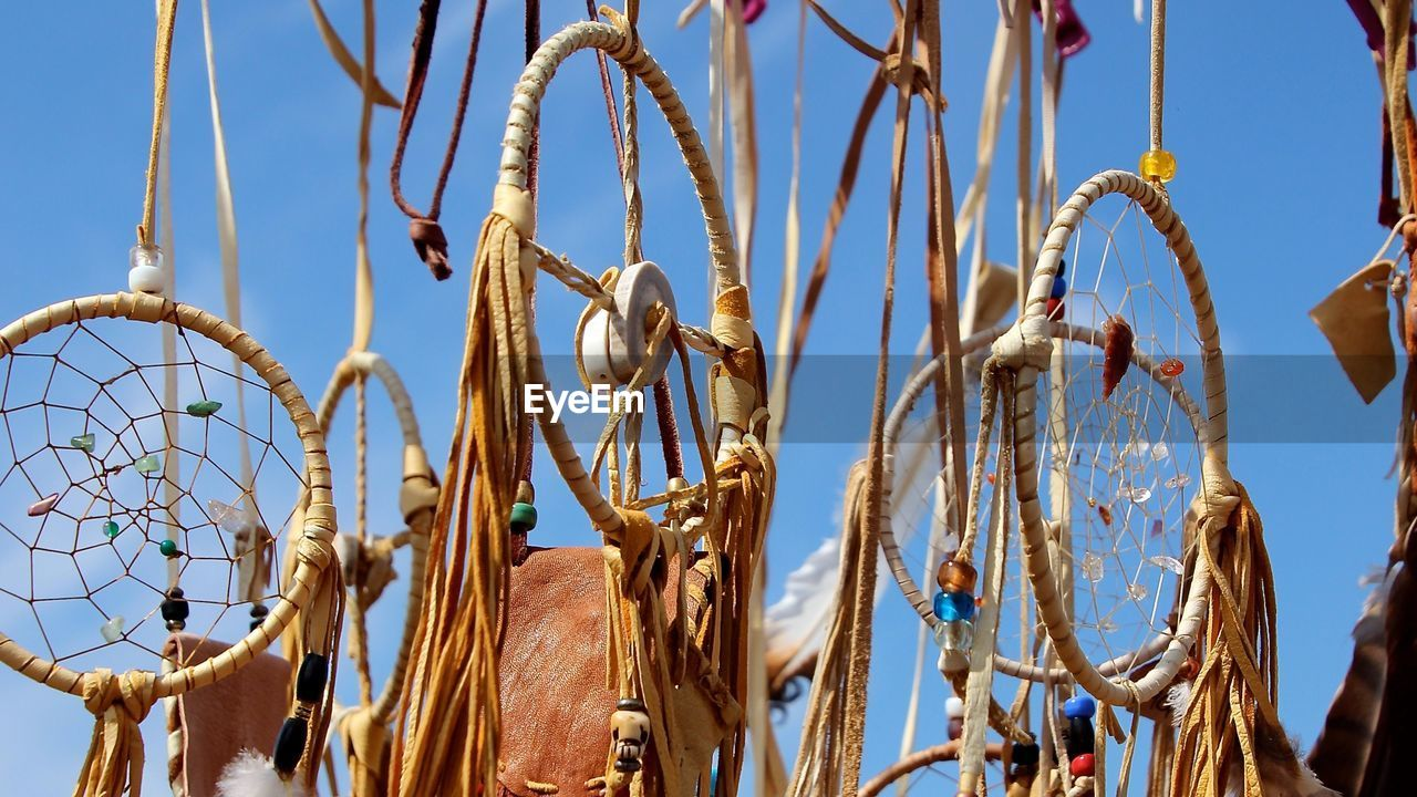 Close-up of dreamcatchers hanging against sky