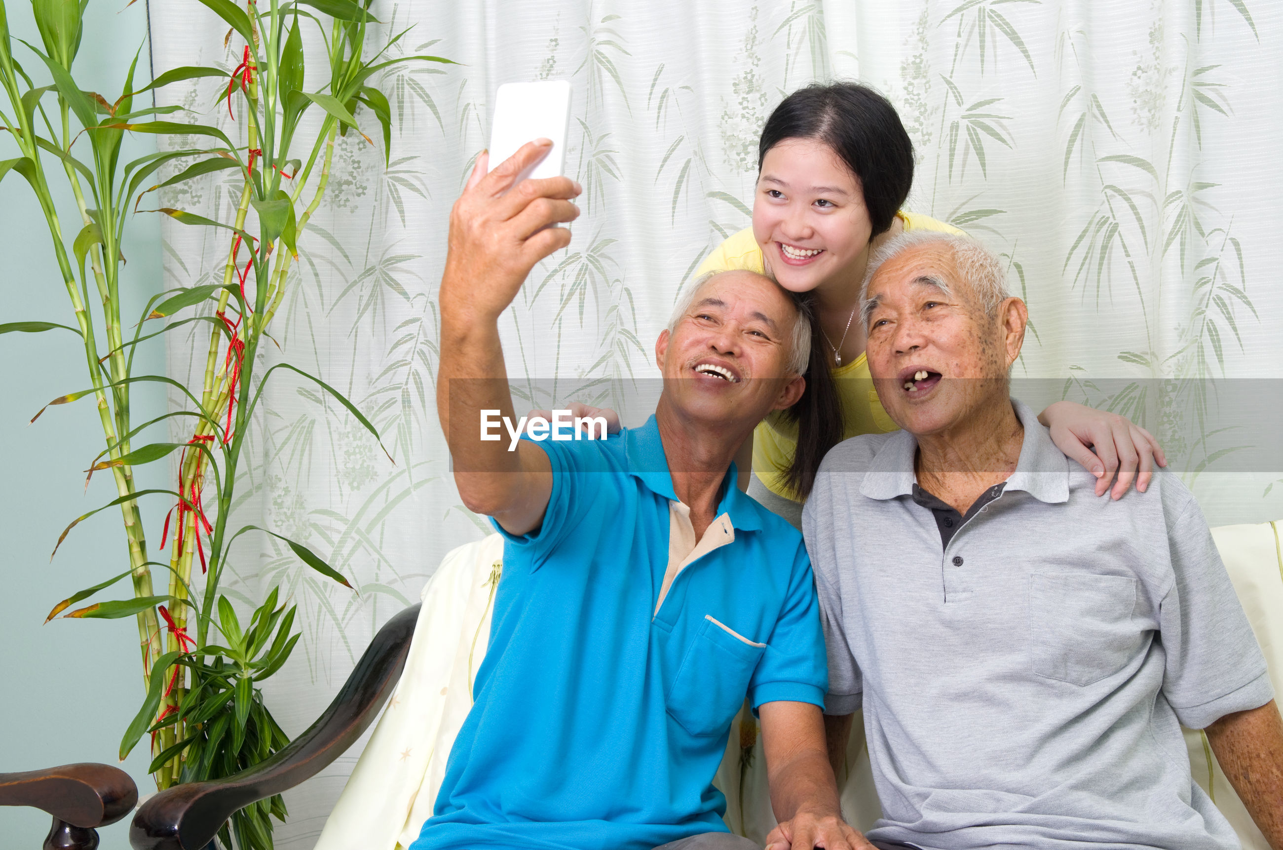 Man taking selfie with friend and woman at home