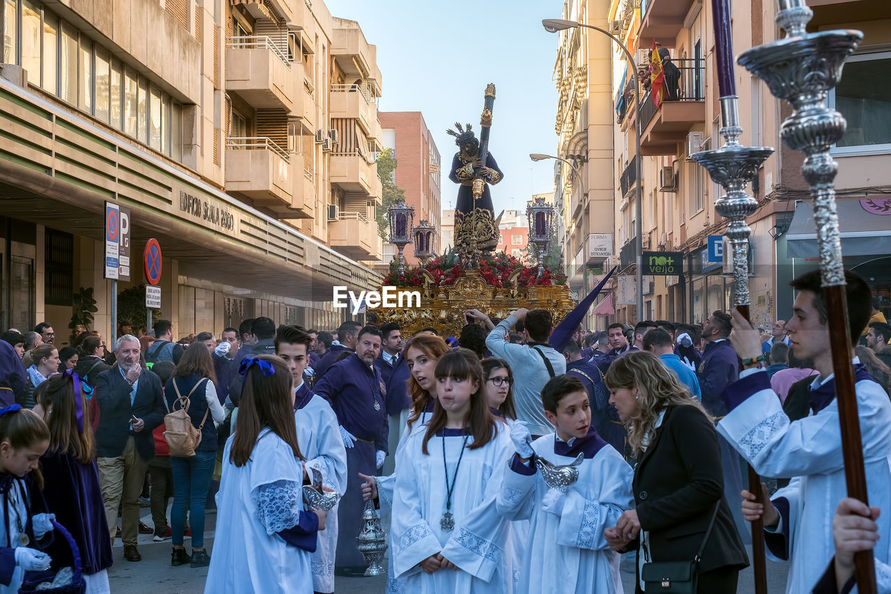 crowd, group of people, large group of people, architecture, real people, city, built structure, building exterior, women, men, adult, religion, street, lifestyles, belief, city life, day, spirituality, human representation, outdoors