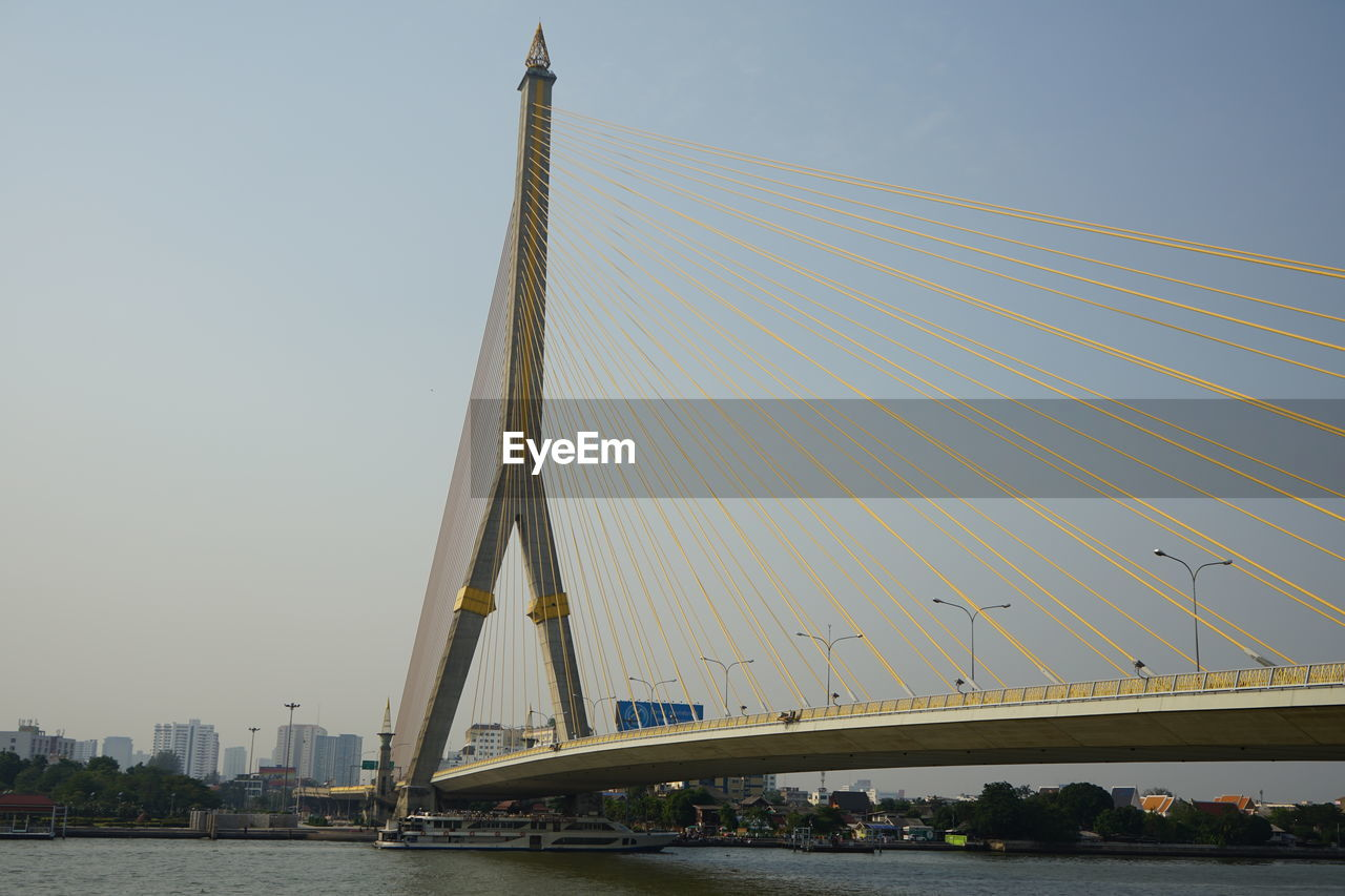 architecture, sky, built structure, bridge, bridge - man made structure, transportation, connection, building exterior, nature, city, engineering, mode of transportation, cable-stayed bridge, land vehicle, clear sky, motor vehicle, water, suspension bridge, outdoors, skyscraper