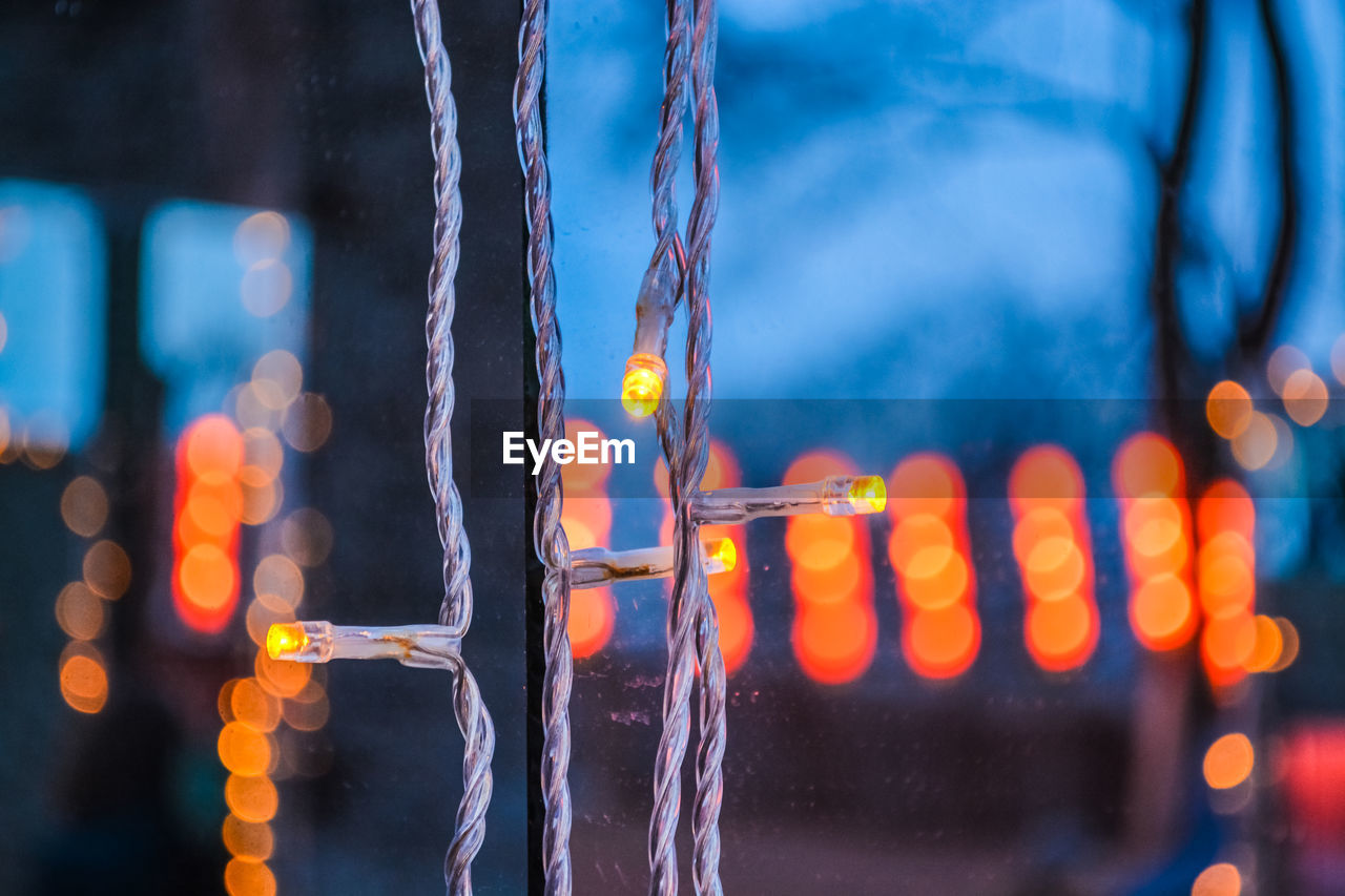 illuminated, focus on foreground, close-up, no people, glowing, night, outdoors, water, selective focus, nature, motion, lighting equipment, blue, metal, multi colored, orange color, light - natural phenomenon, chain, transportation, icicle