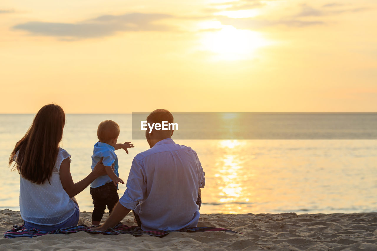 Rear view of family sitting at beach against sky during sunset