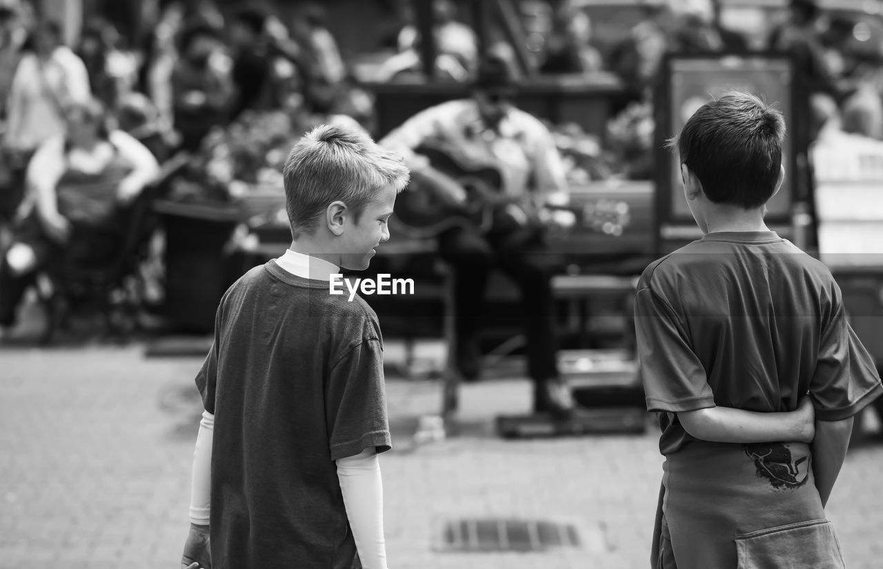 Rear view of boys looking at street musician performing in city