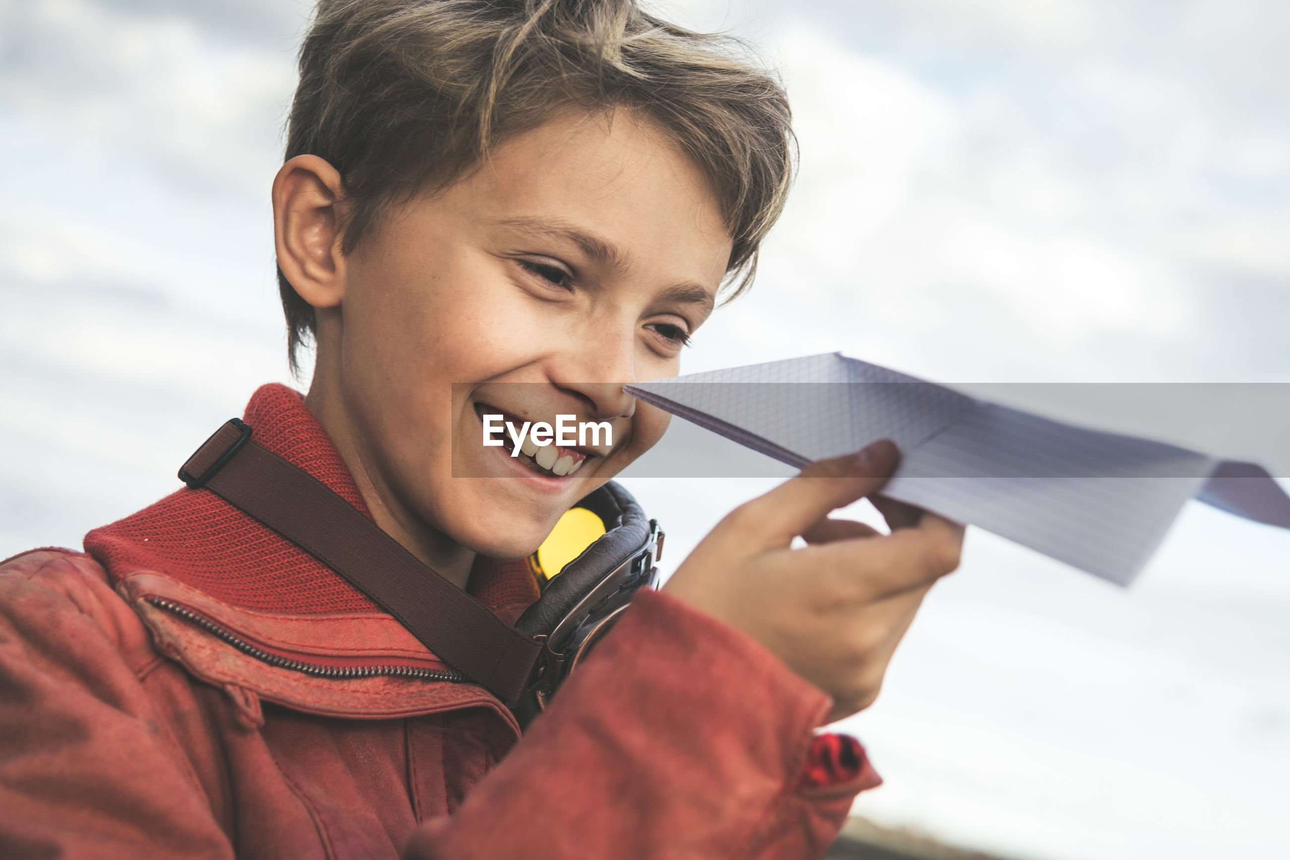 Smiling boy playing with paper airplane against cloudy sky