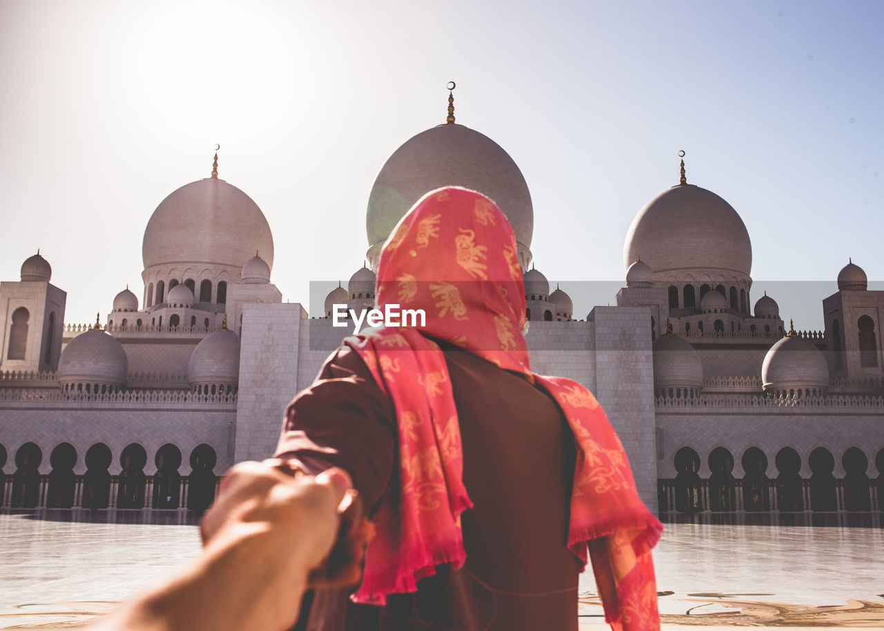 Rear View Of Couple With Holding Hands While Standing Against Mosque